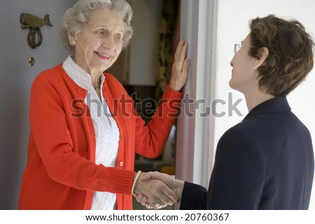 Attractive senior woman shaking hands with visitor at her front door - stock photo