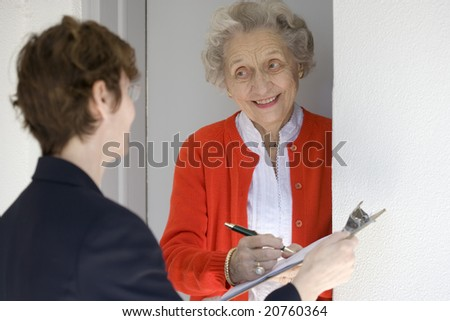 Attractive senior woman signing a document at her front door - stock photo