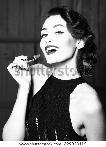 Attractive sensual fashionable retro elegant young adult smiling woman with classic hairstyle and red lips holding lipstick in evening dress indoor on wooden background, vertical picture