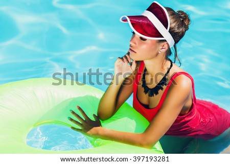 Attractive sensual  woman  with  sportive figure in stylish red one-piece swimsuit  posing  in pool  with  rubber ring, Outdoor fashion portrait of pretty lady enjoying  summertime  on her vacation. - stock photo