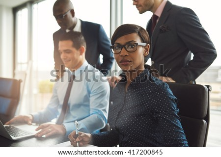 Attractive serious businesswoman wearing eyeglasses and blue blouse sitting at conference table with three male co-workers in front of large bright window - stock photo