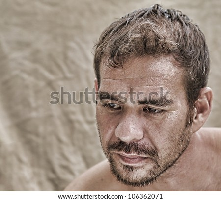 attractive serious man alone, looking down and thinking - stock photo
