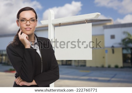 Attractive Serious Mixed Race Woman In Front of Vacant Retail Building and Blank Real Estate Sign. - stock photo