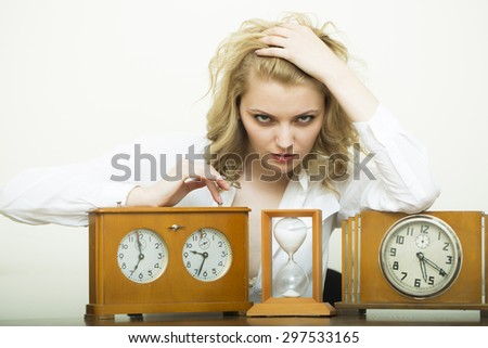 Attractive serious waiting young blonde business woman sitting in shirt with wooden sand glass and clock with dial looking forward on white background, horizontal picture - stock photo
