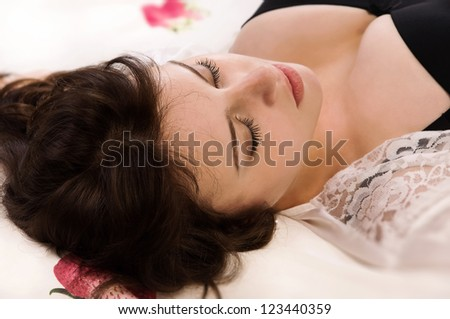 Attractive sexual brunette sleeping on the bed - stock photo