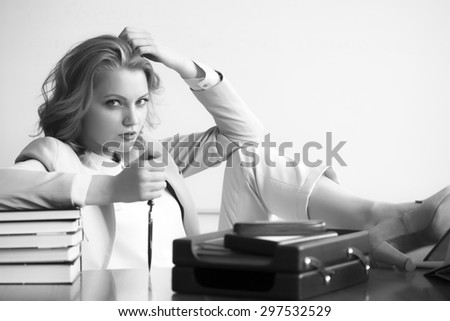 Attractive sexual business woman sitting at table with many office appliances holding knife for cutting paper looking forward black and white copyspace, horizontal picture - stock photo