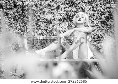 Attractive sexual young pretty girl with beautiful body sitting on bench outdoor in park on natural background black and white, horizontal picture - stock photo