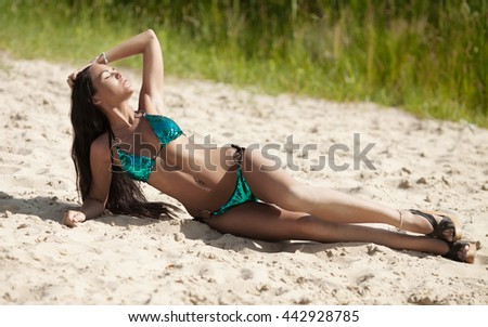 attractive sexy asian woman in bikini, outdoor shot in sand, summer day. Beauty at the beach sand around. Fashion shot of beautiful woman on the beach. - stock photo