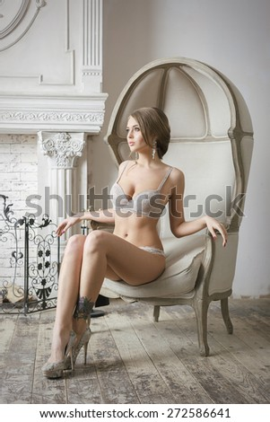 Attractive Sexy Blonde Bride Woman Sitting On Chair In Luxury Interior. Glamour Style Photoshoot. - stock photo