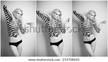 Attractive sexy blonde in black and white tight fit dress and bikini posing provocatively . Portrait of sensual woman in classic boudoir scene against a wall. Beautiful fair hair female, indoor shot. - stock photo