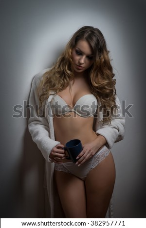 Attractive sexy blonde in white lingerie posing provocatively indoor. Portrait of sensual woman wearing opened bathrobe in classic boudoir scene. Woman with long hair holding a black cup against wall - stock photo