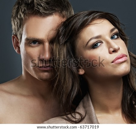 Attractive sexy couple isolated on grey background - stock photo