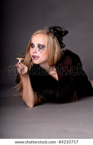 Attractive sexy girl make up as a witch for Halloween eats mushroom, halloween party, halloween costume, halloween witch, woman Halloween, scary halloween, spooky halloween image, vampire woman - stock photo