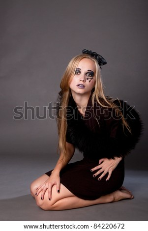 Attractive sexy girl make up as a witch for Halloween sitting on the floor, halloween party, halloween costume, halloween witch, woman Halloween, scary halloween, spooky halloween image, vampire woman - stock photo
