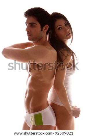 Attractive sexy unsmiling couple dressed in undewear standing back to back, shadowed studio portrait on white - stock photo
