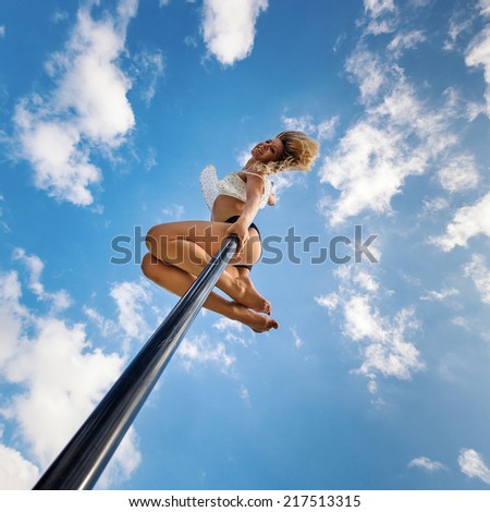 Attractive sexy woman pole dancer performing outdoors against blue cloudy sky. Filtered image. - stock photo