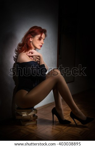 Attractive sexy young woman in black shirt and panties sitting on a pile of books on the floor. Sensual redhead with long legs on high heels shoes shoes posing provocatively against gray wall