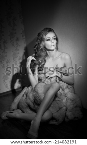 Attractive sexy young woman wrapped in a fur coat sitting in hotel room. Black and white portrait of sensual female daydreaming near a wall. Beautiful girl covered only with fur exposing her shoulders - stock photo