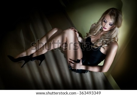 Attractive sexy young woman wrapped in black lingerie sitting on the floor in semidarkness. Sensual blonde on high heels shoes daydreaming near a wall. Beautiful girl with long hair, solitude - stock photo