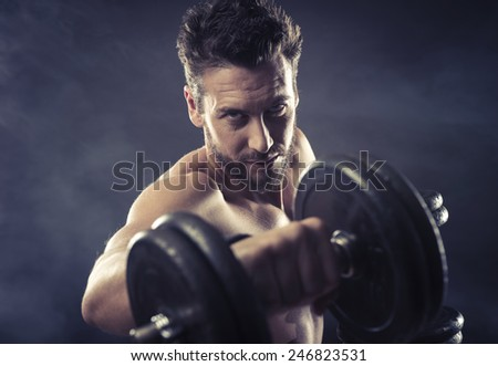 Attractive shirtless man exercising and lifting weights on dark background, strength concept - stock photo