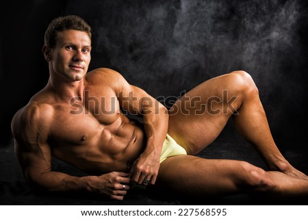 Attractive shirtless muscular man laying down on the floor in bathing suit on dark background - stock photo