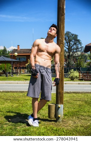 Attractive shirtless young man resting after workout in outdoor gym in city park - stock photo