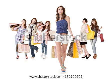 Attractive shopping women walk and look at camera. Group full length portrait. Isolated on the white background. - stock photo