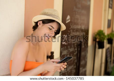 Attractive short haired young woman smiling while writing a message on her mobile phone - stock photo