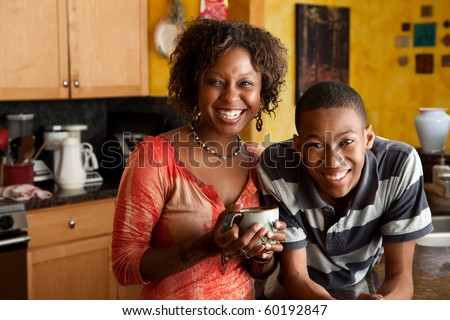 Attractive single-parent mom and son in kitchen - stock photo