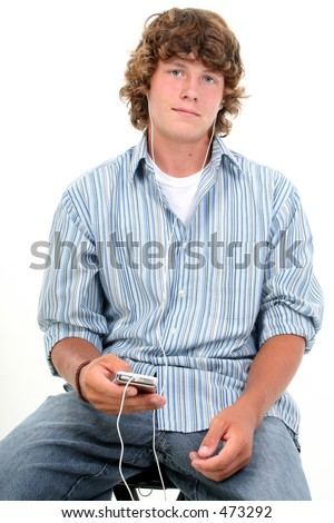 Attractive Sixteen Year Old Teen Boy listening to headphones in casual over white background.  Light brown curly hair and hazel eyes. - stock photo