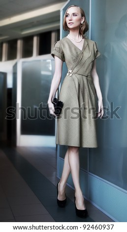 Attractive slender businesswoman fashion model walking in office interior. Business - stock photo