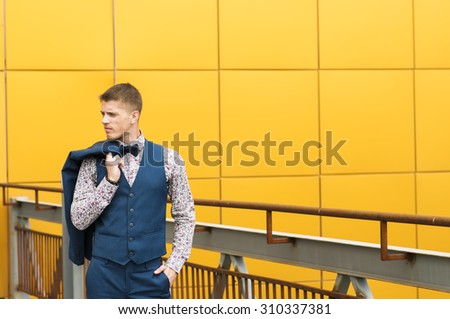 Attractive slender  man in blue suit  posing outdoors. - stock photo