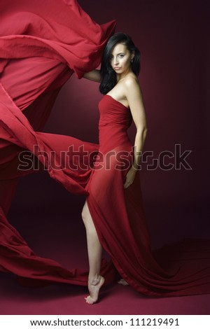 Attractive slender woman in long red fluttering dress on  red background
