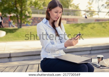 Attractive slender young woman sitting outdoors on an urban park bench reading an sms on her mobile phone with a worried look and her hand to her face - stock photo