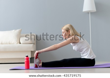 Attractive slim girl is exercising in living room - stock photo