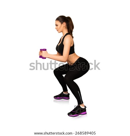 Attractive slim woman concentrated on fitness isolated on white background - stock photo