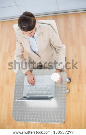 Attractive smart brown haired businesswoman using a laptop while holding a cup of coffee in bright office