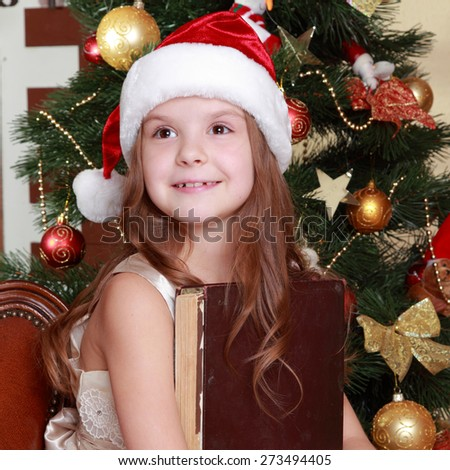 Attractive smiley little girl holding dark brown vintage book over Christmas decoration on Holiday theme/Cheerful young girl wearing santa's hat and holding big ancient book - stock photo