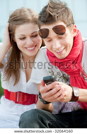 attractive smiley teenagers looking at cellphone - stock photo