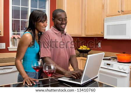 Attractive smiling African American couple standing in a kitchen looking at a laptop that is on a counter next to two wine glasses.