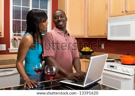 Attractive smiling African American couple standing in a kitchen, looking at each others eyes, while using a laptop that is on a counter next to two wine glasses. - stock photo