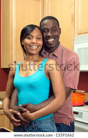 Attractive smiling African American couple standing in a kitchen. Vertically framed shot with the man and woman looking at the camera.