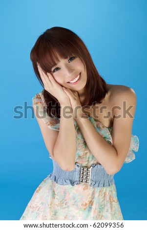 Attractive smiling beauty, closeup portrait of Asian over blue background. - stock photo