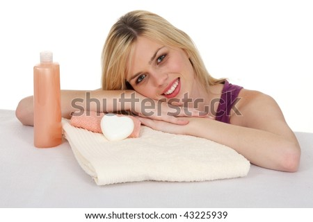 Attractive smiling blond girl with spa towels and soaps