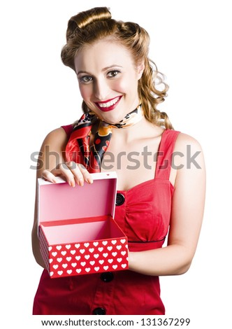 Attractive smiling blond woman in red dress holding gift box with lid open and decorated with red heart-shapes on white background - stock photo