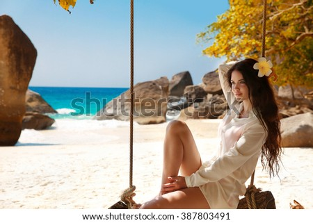 Attractive smiling brunette summer portrait on exotic vacation. Beautiful sensual woman with long healthy hair sitting on a swing. Good life. - stock photo