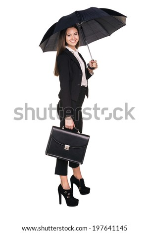 Attractive smiling business woman holding up a black portfolio case and an umbrella with one leg up standing on one foot on white background - stock photo