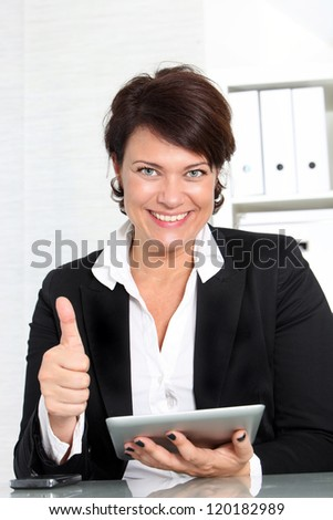 Attractive smiling businesswoman seated at her desk with a tablet in her hand giving thumbs up of approval - stock photo