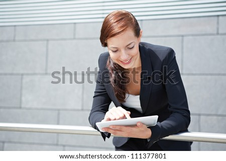 Attractive smiling businesswoman with tablet computer on the way - stock photo