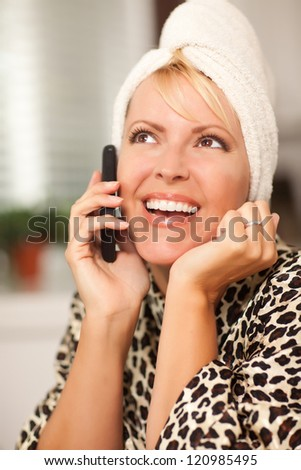 Attractive Smiling Caucasian Woman Talking on Her Cell Phone with a Towel on Her Head. - stock photo